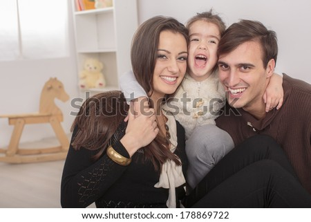 Happy family sitting in the room - stock photo