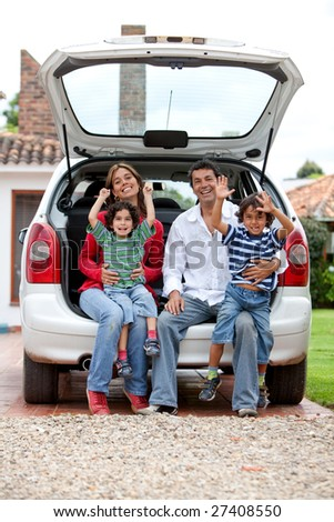 Happy family sitting in the trinck of their car - stock photo