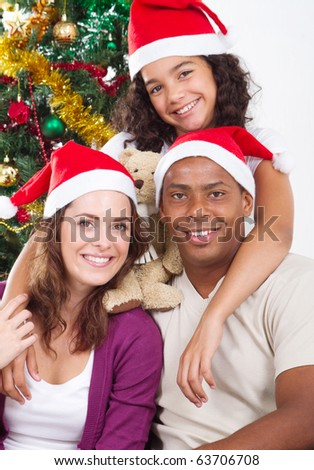 happy family sitting near Christmas tree - stock photo