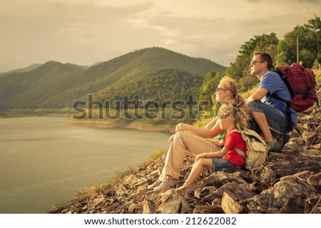 Happy family sitting near the lake at the day time. Concept of friendly family. - stock photo