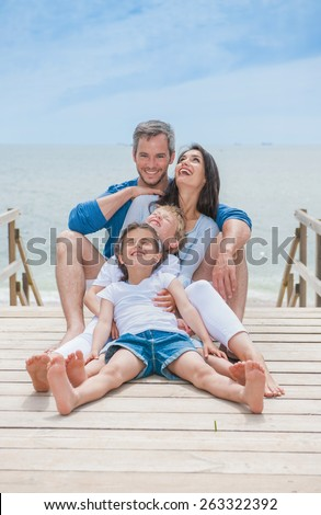 happy family sitting on a wooden pontoon in front of the sea - stock photo
