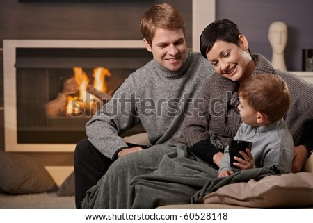 Happy family sitting on couch at home in front of fireplace, smiling. - stock photo