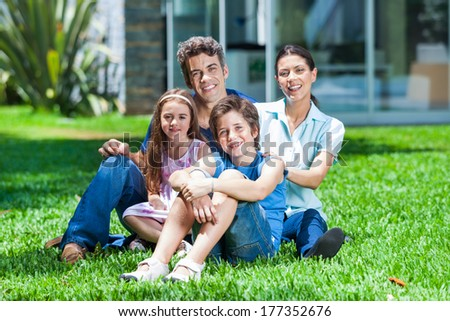 happy family sitting on grass in front of house, parents with two children smile - stock photo