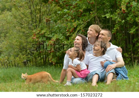 Happy family sitting on grass in summer park