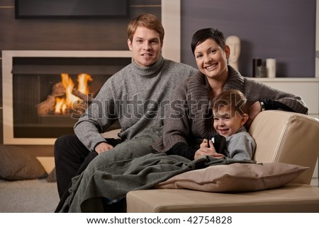 Happy family sitting on sofa at home in front of fireplace, looking at camera, smiling.