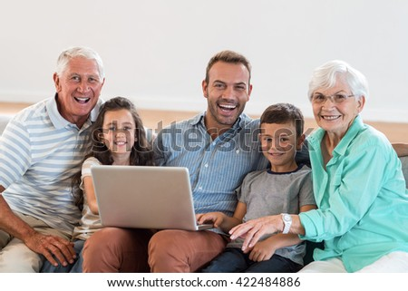 Happy family sitting on sofa using a laptop in living room - stock photo