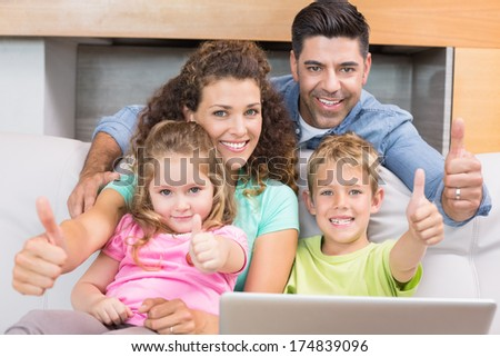 Happy family sitting on sofa using laptop giving thumbs up at home in living room - stock photo