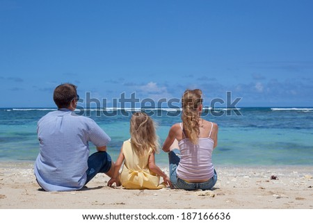 Happy family sitting on the beach in the day time