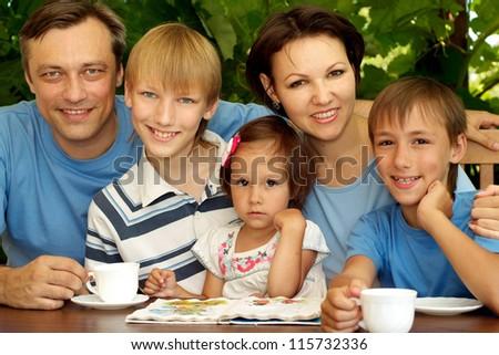 Happy family sitting on the veranda of his cottage - stock photo
