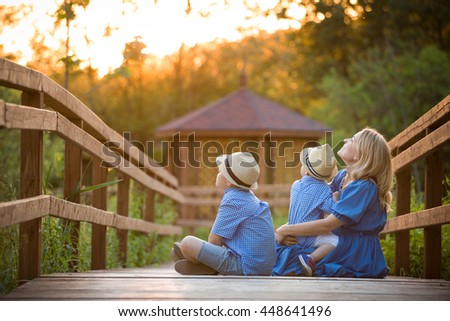 Happy family sitting on the wooden bridge in the park and having fun on sunset outdoors. Mother with kid boy and little toddler boy walking in the park on a sunny day. Smiling woman with children. - stock photo