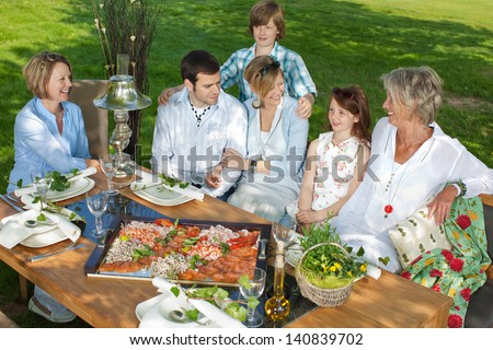 happy family sitting together at dining table in the garden - stock photo
