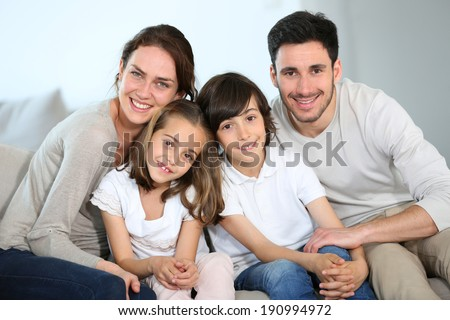 Happy family sitting together in couch - stock photo