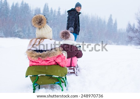 Happy family sledding in winter outdoors - stock photo