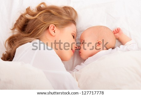 happy family sleeping together. mother embraces the newborn baby in bed