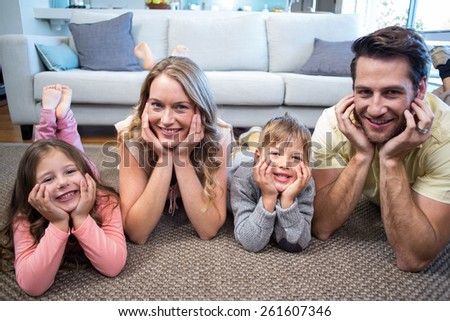 Happy family smiling at camera at home in the living room - stock photo