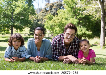 Happy family smiling at camera on a sunny day