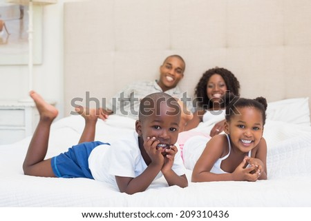Happy family smiling at camera together on bed at home in the bedroom - stock photo