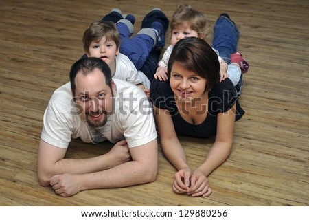 Happy family smiling at home lying together on wooden floor