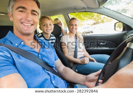 Happy family smiling at the camera in the car on a sunny day - stock photo