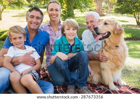 Happy family smiling at the camera with their dog on a sunny day - stock photo