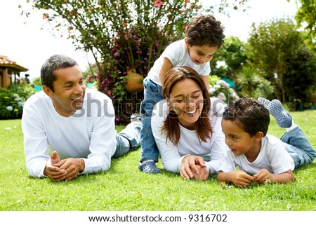 happy family smiling in a portrait of a mum and dad with their two kids