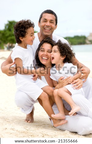 happy family smling at the beach while on vacation - stock photo