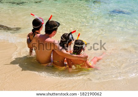 Happy family snorkeling and having fun on tropical beach vacation  - stock photo