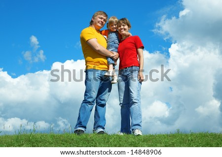 happy family stand on green grass under sky with clouds - stock photo