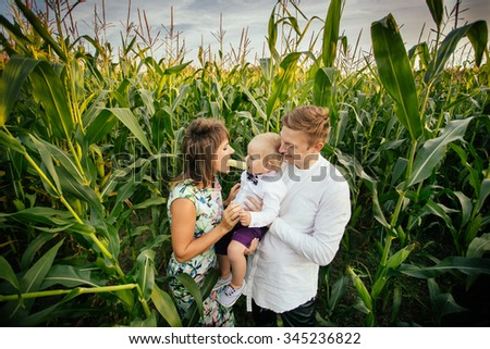Happy family standing in a large corn field in the Summer, mom and son eating corn on the cob. - stock photo