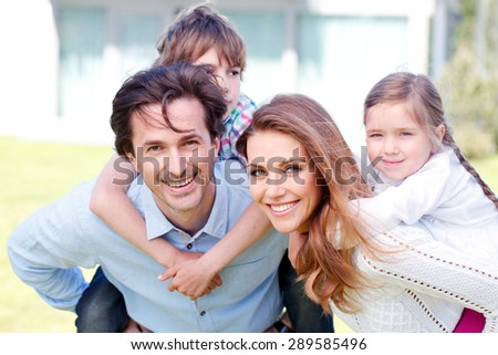 happy family standing in front of the house - stock photo
