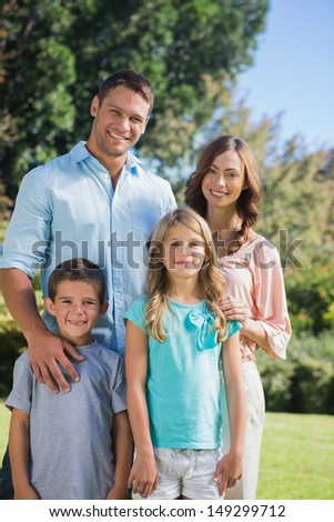 Happy family standing in the countryside smiling at camera