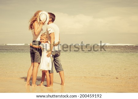 Happy family standing on the beach at the day time - stock photo