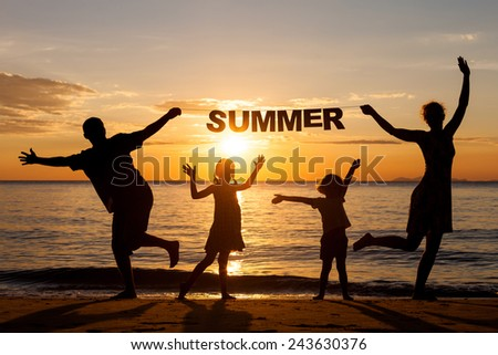 "Happy family standing on the beach at the sunset time. Parents hold in the hands  inscription ""Summer"". Concept of friendly family."
