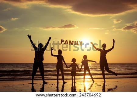 "Happy family standing on the beach at the sunset time. Parents hold in the hands  inscription ""Family"". Concept of friendly family."
