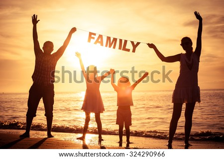 "Happy family standing on the beach at the sunset time. Parents hold in the hands  inscription ""Family"". Concept of happy family. - stock photo"