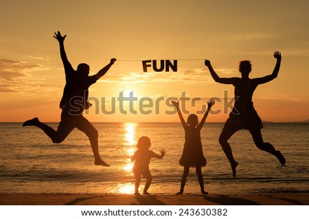 "Happy family standing on the beach at the sunset time. Parents hold in the hands  inscription ""Fun"". Concept of friendly family."