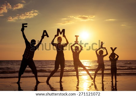 "Happy family standing on the beach at the sunset time. They keep the letters forming the word "" family"". Concept of friendly family."