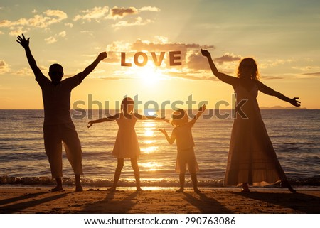 "Happy family standing on the beach at the sunset time. They keep the letters forming the word "" love"". Concept of friendly family. - stock photo"