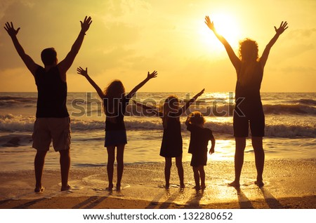 Happy family standing on the beach on the dawn time - stock photo