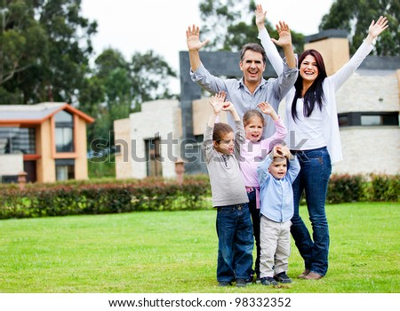 Happy family standing outdoors at the backyard wih arms up - stock photo