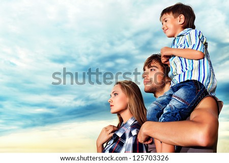 Happy family standing together over beautiful cloudy sky. - stock photo