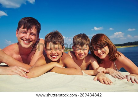 Happy family sunbathing on sandy beach - stock photo