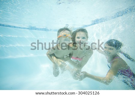 Happy family swimming underwater. Mother, son and daughter having having fun in pool. - stock photo