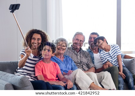 Happy family taking a selfie in living room at home - stock photo