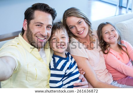 Happy family taking selfie on couch at home in the living room - stock photo