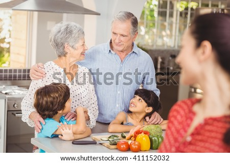 Happy family talking in kitchen at home - stock photo