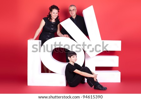 Happy family, three of them with the words Love. studio photography - stock photo