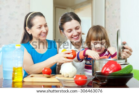 Happy family together cooking vegetarian lunch with vegetables   - stock photo