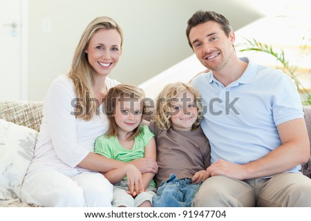 Happy family together on the couch - stock photo