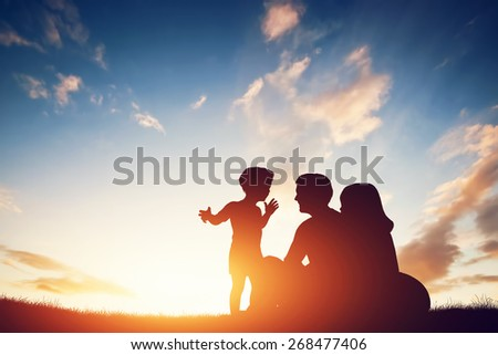 Happy family together, parents with their little child sitting on grass at sunset - stock photo